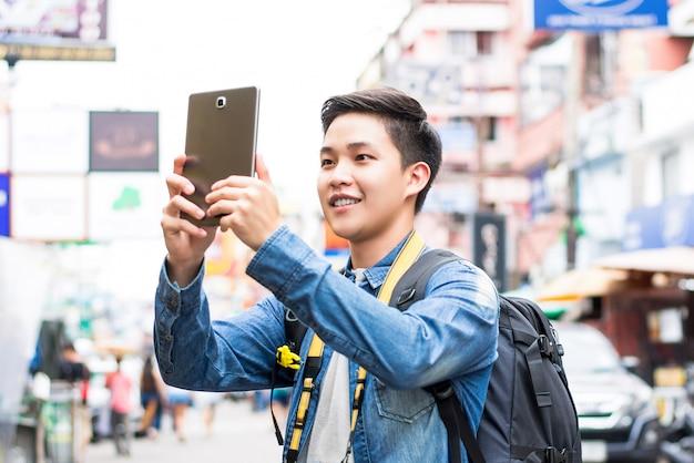 Foto di presa turistica asiatica con il computer della compressa mentre viaggiando a bangkok, tailandia
