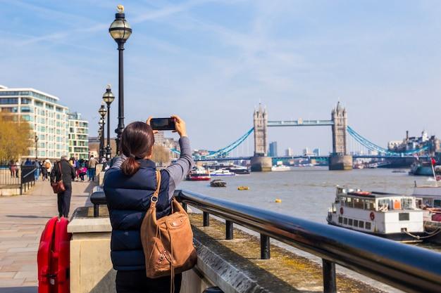 Foto di presa turistica della donna sul tower bridge con la macchina fotografica del telefono cellulare.