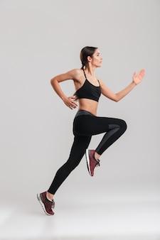 Foto di profilo del corridore femminile atletico ben costruito nell'addestramento degli abiti sportivi, isolato lungo la parete grigia