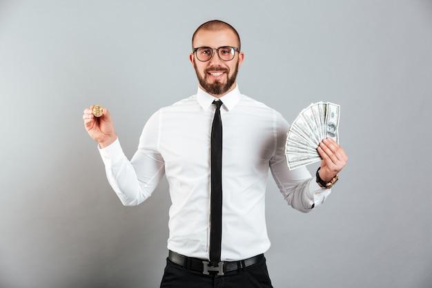 Foto di ricco uomo 30s in bicchieri e tuta mostrando bitcoin e un sacco di soldi valuta del dollaro, isolato su muro grigio