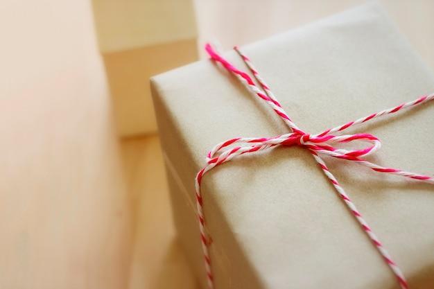 Foto di stile vintage della scatola pacchetto marrone con corda rossa collocata su un tavolo di legno.