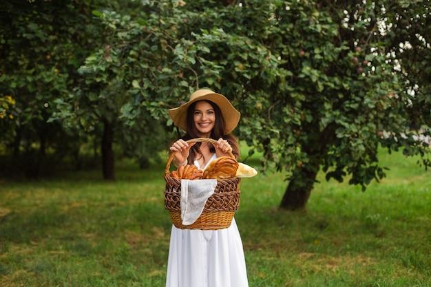 Foto di stock ritratto di una bella donna bruna in cappello estivo e abito bianco dimostrando prodotti da forno freschi fatti in casa in cestino marrone wattled nelle sue mani in piedi nel parco verde il giorno d'estate.