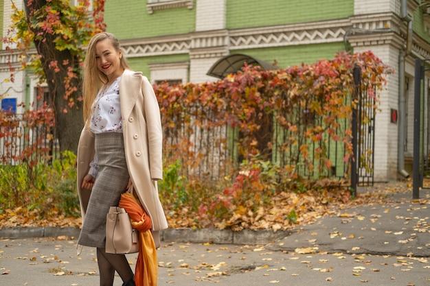 Foto di strada di giovane bella donna che indossa abiti classici alla moda. modello guardando in basso. concetto di moda femminile.