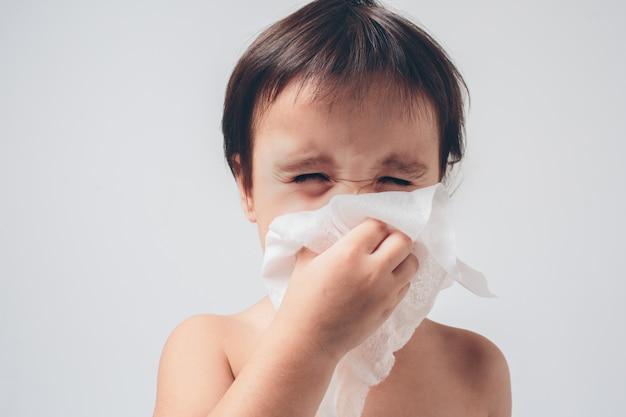 Foto di studio di un bambino con fazzoletto. il bambino malato isolato ha il naso che cola.