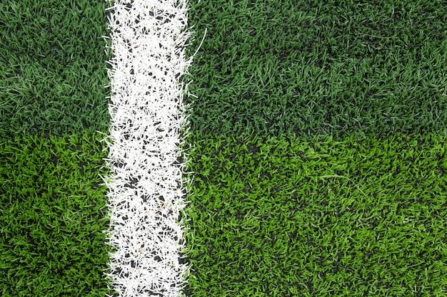 Foto di un campo sportivo di erba sintetica verde con colpo di linea bianca