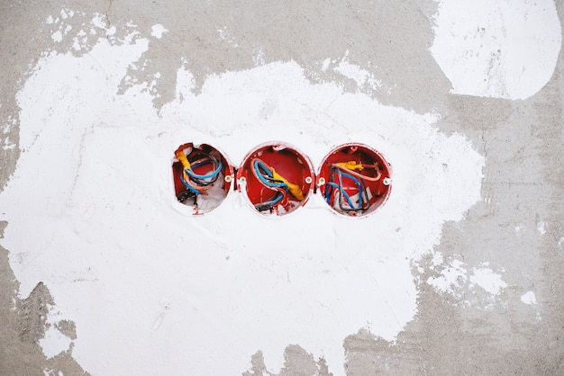 Foto di un muro, con fori di scatola elettrica, processi di costruzione