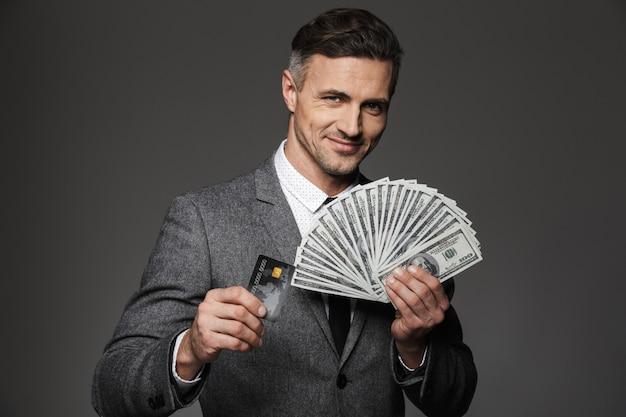 Foto di un ragazzo fortunato anni '30 in giacca e cravatta che dimostra il premio in denaro in banconote da un dollaro e carta di credito, isolato sopra il muro grigio