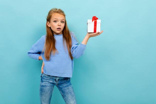 Foto di una bella studentessa sorpresa con una confezione regalo
