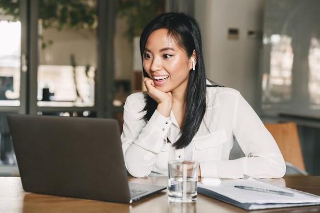 Foto di una donna asiatica 20s eccitata che indossa una camicia bianca e auricolari bluetooth che sorride, mentre guarda il computer portatile seduto al tavolo in ufficio