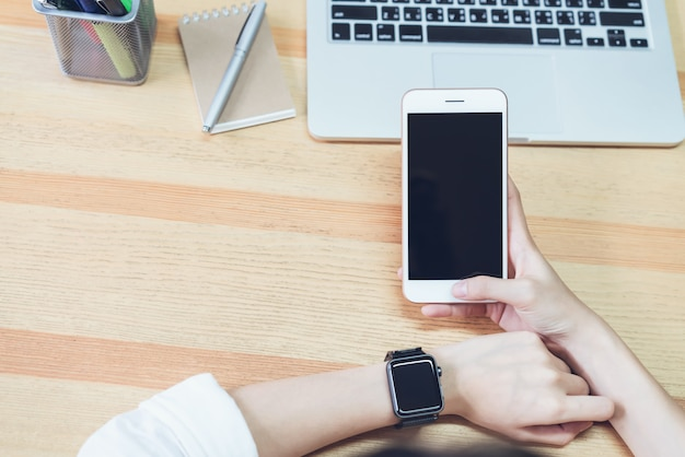 Foto di una donna in possesso di un telefono schermo vuoto e un computer. e metti un orologio intelligente.