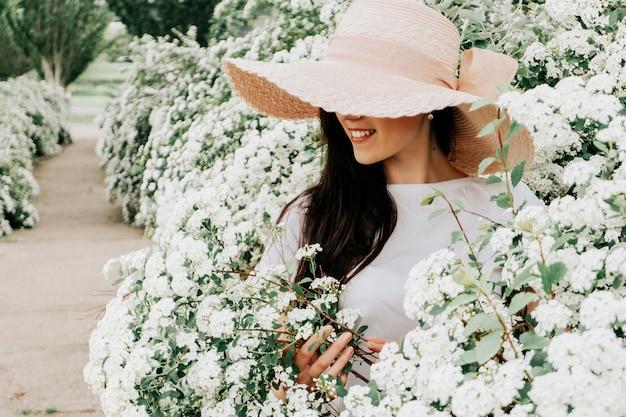 Foto di una donna in un cappello e fiori.