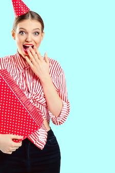 Foto di una donna sorpresa che ha ricevuto una confezione regalo per il suo compleanno