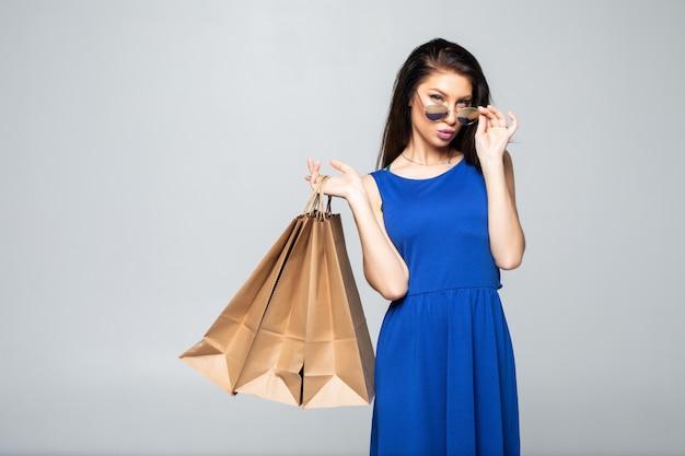 Foto di una giovane donna attraente che ostacola i sacchetti della spesa isolati