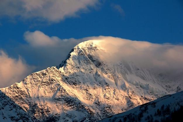 Foto di una montagna innevata con un ghiacciaio e nuvole spazzate via dal vento