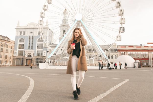 Foto di una ragazza alla moda a tutta altezza, che cammina lungo la strada con una tazza di caffè in mano, indossa un cappotto, guarda nell'obiettivo e corregge i suoi capelli