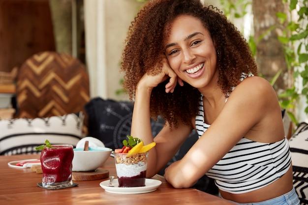 Foto di una studentessa di razza mista spensierata si riposa dopo una dura giornata di lavoro all'università e ha superato un esame difficile, mangia gustosi dessert, dimostra un sorriso caldo e positivo soddisfatto dei risultati