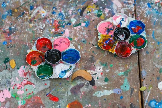 Foto di una tavolozza di artisti caricata con varie vernici di colore sullo sfondo tavolo in legno
