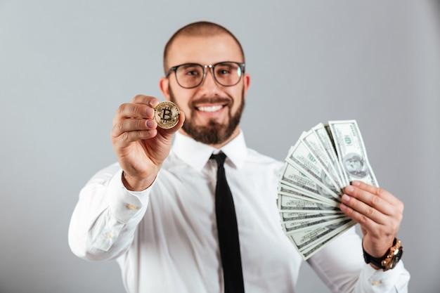 Foto di uomo economista in bicchieri e tuta mostrando bitcoin a fuoco e in possesso di un sacco di soldi valuta dollaro, isolato su muro grigio