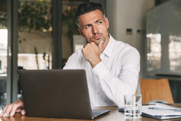 Foto di uomo europeo che indossa una camicia bianca e auricolari seduti a tavola in ufficio con sguardo meditabondo da parte, mentre si lavora al computer portatile