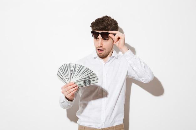 Foto di uomo fortunato sorpreso in camicia che toglie gli occhiali da sole neri e guardando un fan di banconote in dollari di denaro con eccitazione, isolato su un muro bianco con ombra