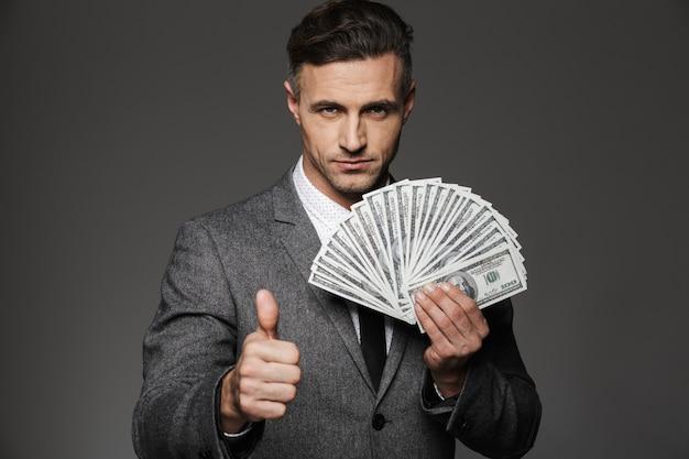 Foto di uomo ricco 30s in tailleur che tiene fan di valuta dollaro denaro contante e che mostra il pollice in su, isolato sopra il muro grigio