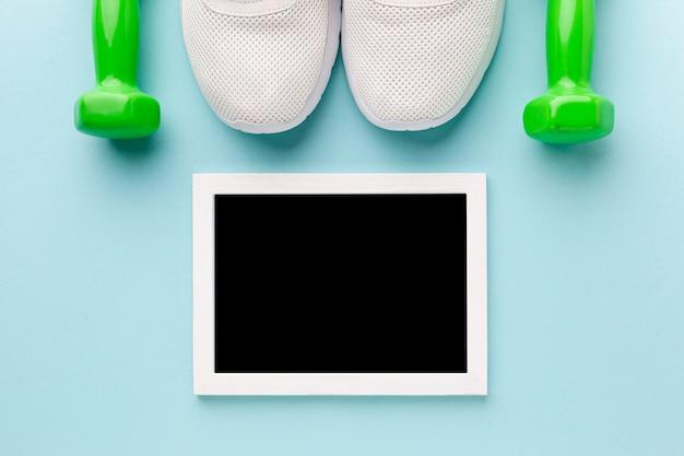 Foto di vista dall'alto mock up accanto a scarpe da ginnastica e pesi