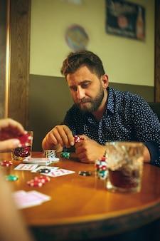 Foto di vista laterale degli amici che si siedono alla tavola di legno. amici che si divertono mentre giocano a gioco da tavolo.