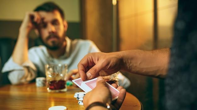Foto di vista laterale di amici seduti al tavolo di legno. amici che si divertono durante il gioco da tavolo.