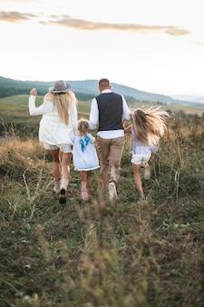 Foto di vista posteriore della famiglia allegra in abiti alla moda, genitori e figli, godendo e correndo insieme in montagna