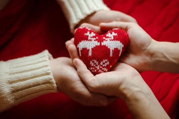 Foto di vista superiore della mano maschile e femminile con cuore a maglia.