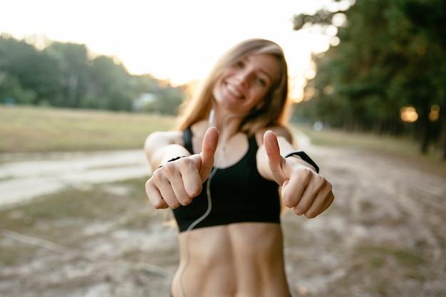 Foto esterna della ragazza sportiva in canottiera sportiva, mostrando un pollice in su, allegramente sorridente