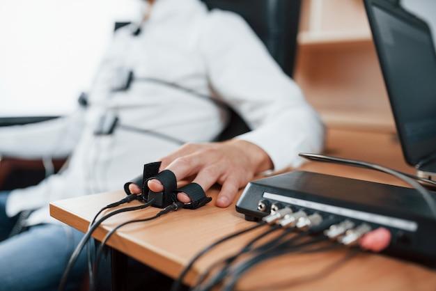Foto focalizzata. l'uomo sospettoso passa alla macchina della verità in ufficio. fare domande. test del poligrafo