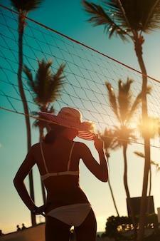 Foto in stile retrò di ragazza modello sexy in bikini bianco con rete da pallavolo sulla spiaggia e palme dietro il cielo estivo blu