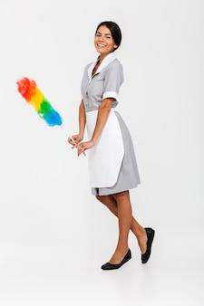 Foto integrale della governante attraente che posa con lo spolveratore variopinto
