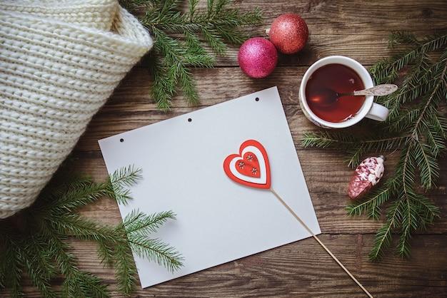 Foto invernale: una tazza di tè, rami di abete, decorazioni natalizie, una sciarpa e un foglio di carta con un cuore su un bastone