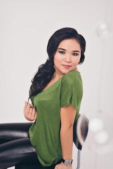 Foto isolata: bellissima modella con i capelli lunghi mostra i vestiti. modellistica, abbigliamento casual