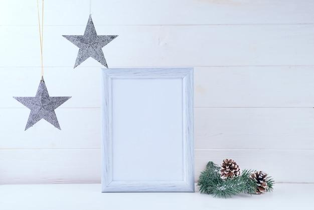 Foto mock up con cornice bianca, stelle e rami di pino su legno bianco