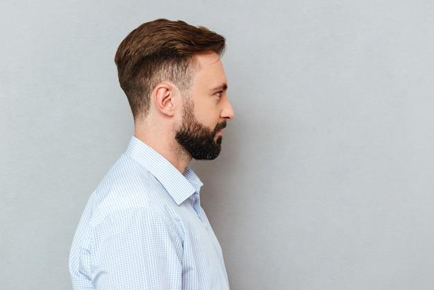 Foto nel profilo dell'uomo barbuto nella posa dei vestiti di affari
