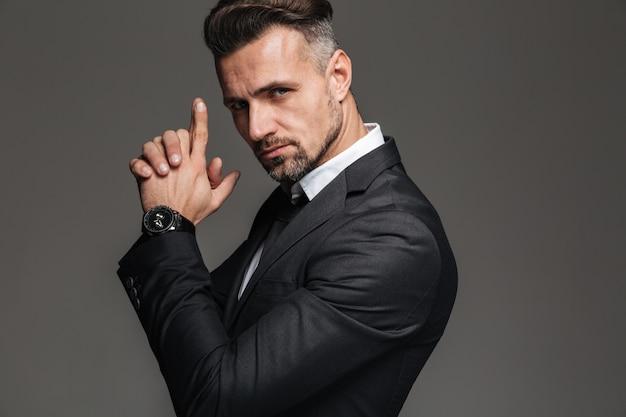 Foto nel profilo di un elegante uomo adulto anni '30 in abito nero guardando la telecamera con vista difficile e tenendosi per mano come una pistola, isolato su grigio scuro