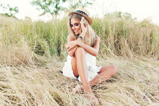 Foto orizzontale full-lengh della ragazza bionda carina con i capelli lunghi in posa per la telecamera sul fieno. indossa cappello, abito bianco e guarda in basso.