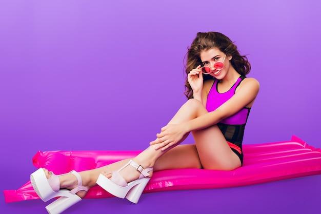 Foto orizzontale integrale della ragazza attraente con capelli ricci lunghi in occhiali da sole rosa su sfondo viola in studio. indossa il costume da bagno che si siede sul materasso ad aria rosa.