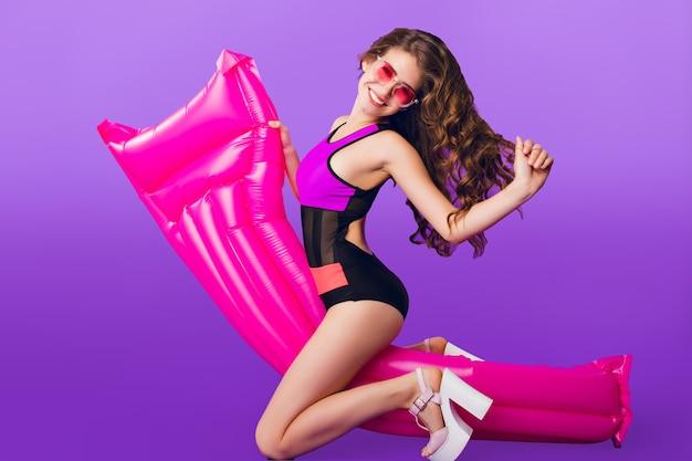 Foto orizzontale integrale della ragazza attraente con capelli ricci lunghi in occhiali da sole rosa su sfondo viola in studio. indossa il costume da bagno e si diverte con il materasso ad aria rosa.