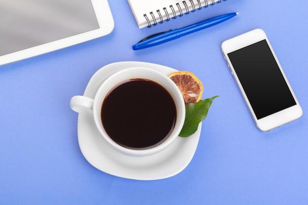 Foto piana di disposizione con il taccuino, tazza di caffè sul blu