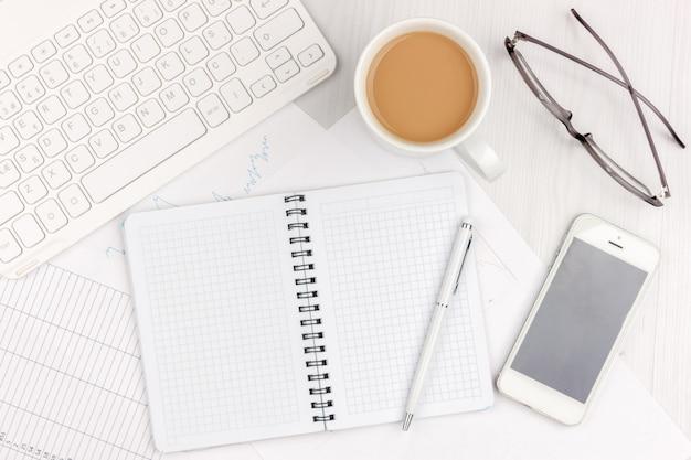 Foto piana di disposizione della scrivania bianca con il computer portatile, lo smartphone, gli occhiali, il taccuino e la penna con il fondo dello spazio della copia. modello