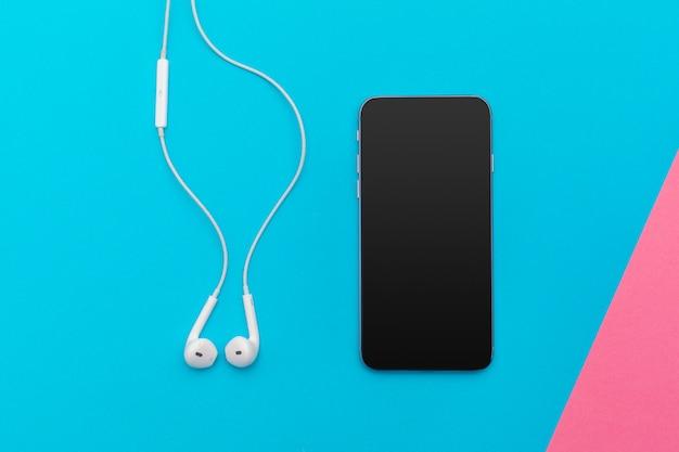 Foto piatta e creativa della scrivania dell'area di lavoro con auricolari e telefono cellulare