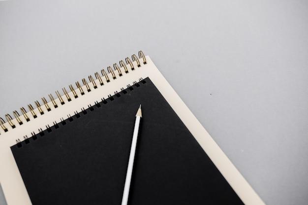 Foto piatta e creativa della scrivania dell'area di lavoro con quaderni bianchi e neri