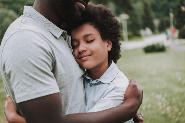 Foto potata del figlio sorridente abbraccia suo padre