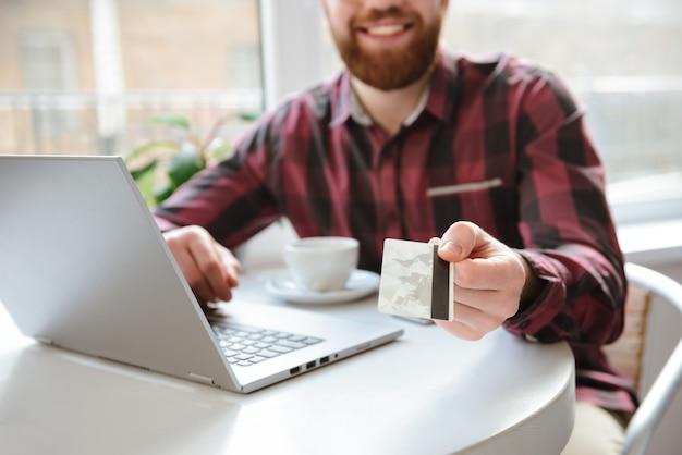 Foto potata del giovane barbuto allegro che mostra la carta di debito
