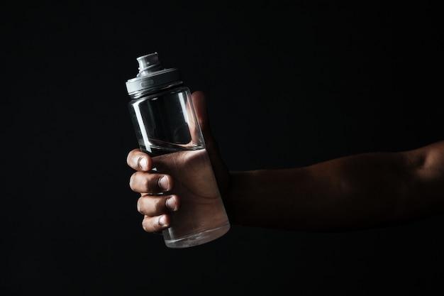 Foto potata della bottiglia afroamericana della tenuta della mano dei maschi con acqua