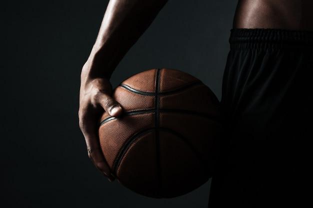 Foto potata della palla della tenuta del giocatore di pallacanestro